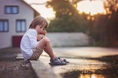 Niño pequeño triste, sentándose en la calle en la lluvia, abrazando su t Fotografía de archivo