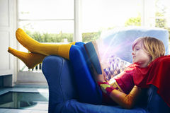 Niño pequeño vestido como superhéroe que lee un libro Fotos de archivo libres de regalías