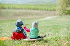 Niño pequeño y bebé que se sientan en un fondo del paisaje verde foto de archivo