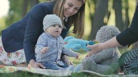 Niño pequeño y dos mujeres que se relajan en un parque en la sobrecama metrajes