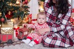 Niño pequeño y mamá que sostienen un regalo Día de fiesta del ` s del Año Nuevo, preparación para la Navidad tren de la familia Imágenes de archivo libres de regalías