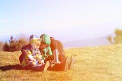 Niño pequeño y muchacha con las mochilas que tienen resto en montañas Foto de archivo libre de regalías