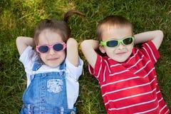 Niño pequeño y muchacha dulces, vidrios que llevan, sonrisa, poniendo en t foto de archivo