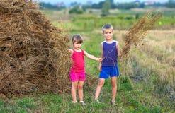 Niño pequeño y muchacha en campo cerca del pajar Foto de archivo