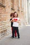 Niño pequeño y muchacha en la calle fotos de archivo