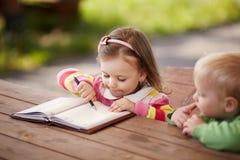 Niño pequeño y muchacha que aprenden escribir imágenes de archivo libres de regalías
