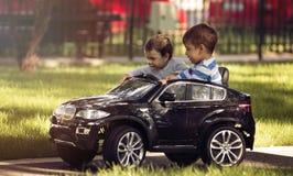 Niño pequeño y muchacha que conducen el coche del juguete en un parque