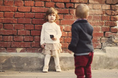 Niño pequeño y muchacha que juegan con el teléfono Imágenes de archivo libres de regalías
