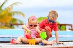 Niño pequeño y muchacha que juegan en piscina en Foto de archivo libre de regalías