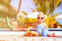 Niño pequeño y muchacha que juegan en piscina en Fotografía de archivo