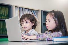 Niño pequeño y muchacha que juegan a los juegos de ordenador Pequeño muchacho y muchacha que atan con el ordenador portátil imagen de archivo