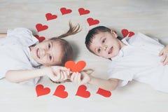 Niño pequeño y muchacha que mienten en el piso Fotos de archivo libres de regalías