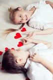 Niño pequeño y muchacha que mienten en el piso Foto de archivo libre de regalías