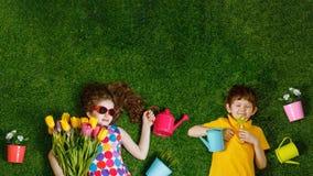 Niño pequeño y muchacha que mienten en un césped verde imagen de archivo libre de regalías