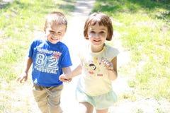 Niño pequeño y muchacha que se ejecutan en el parque Imagenes de archivo