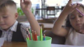 Niño pequeño y muchacha que toman los lápices del color para las imágenes de dibujo en el papel Dibujo de Brother y de la hermana almacen de video