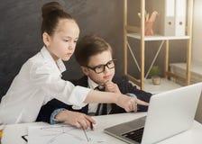 Niño pequeño y muchacha que trabajan en el ordenador portátil imagenes de archivo