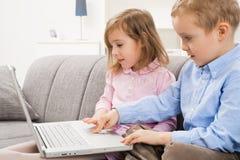 Niño pequeño y muchacha que usa la computadora portátil Imagen de archivo libre de regalías