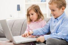 Niño pequeño y muchacha que usa la computadora portátil Imágenes de archivo libres de regalías