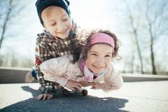 Niño pequeño y muchacha skaiting en la calle Imagenes de archivo