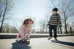Niño pequeño y muchacha skaiting en la calle Imagen de archivo
