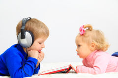 Niño pequeño y niña pequeña con las auriculares usando Imagen de archivo