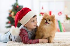 Niño pequeño y perro felices del niño en la Navidad Foto de archivo libre de regalías