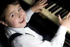 Niño pequeño y piano. Foto de archivo