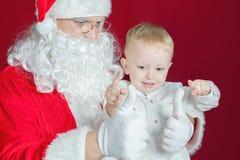 Niño pequeño y Santa Claus en el día de fiesta de la Navidad Foto de archivo libre de regalías