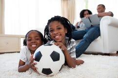 Niño pequeño y su balón de fútbol de la explotación agrícola de la hermana imágenes de archivo libres de regalías