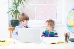 Niño pequeño y su hermana linda del niño con el ordenador portátil Foto de archivo