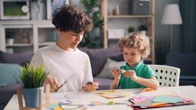 Niño pequeño y su mamá que hacen corte del collage las figuras de papel que se pegan con pegamento almacen de metraje de vídeo
