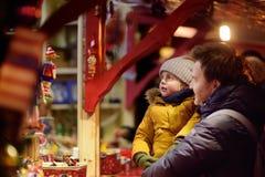 Niño pequeño y su padre que tienen tiempo maravilloso en mercado de Navidad fotos de archivo
