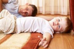 Niño pequeño y su reclinación del padre Fotos de archivo libres de regalías