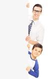 Niño pequeño y un adulto joven que se coloca detrás del panel en blanco Fotos de archivo