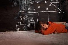 Niño pobre en la calle que piensa en los regalos de la Navidad imagenes de archivo