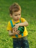 Niño positivo lindo, jugando feliz con la bola en prado verde Foto de archivo libre de regalías