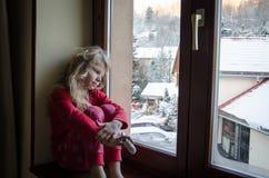 Niño precioso que mira a través de ventana Imagen de archivo libre de regalías