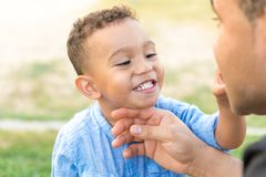 Niño precioso que muestra los dientes a su padre imagenes de archivo