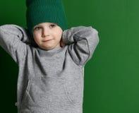 Niño preescolar del muchacho que se coloca en suéter de la sudadera con capucha y sombrero grises del invierno en verde Fotografía de archivo libre de regalías
