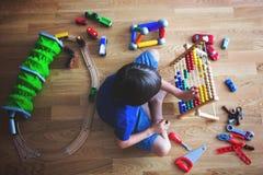 Niño preescolar, jugando con el ábaco y otros juguetes, sentándose encendido Fotografía de archivo libre de regalías