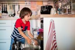 Niño preescolar, muchacho, mamá de ayuda, poniendo platos sucios en dishw foto de archivo