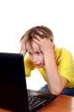 Niño preocupado con el ordenador portátil Fotos de archivo libres de regalías