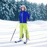 Niño profesional del esquiador que lleva una ropa de deportes con los esquís en invierno Foto de archivo