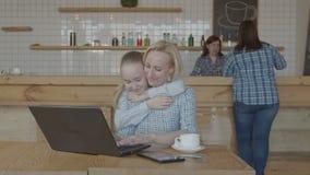 Niño que abraza establecimiento de una red de la madre en el ordenador portátil en café metrajes