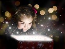 Niño que abre un rectángulo de regalo mágico Imagen de archivo libre de regalías