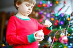 Niño que adorna el árbol de navidad con las bolas Fotografía de archivo