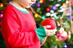Niño que adorna el árbol de navidad con las bolas Foto de archivo libre de regalías