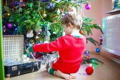Niño que adorna el árbol de navidad con las bolas Imágenes de archivo libres de regalías