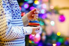 Niño que adorna el árbol de navidad con las bolas Foto de archivo